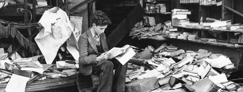 """A boy sits amid the ruins of a London bookshop following an air raid on October 8, 1940, reading a book titled """"The History of London."""""""